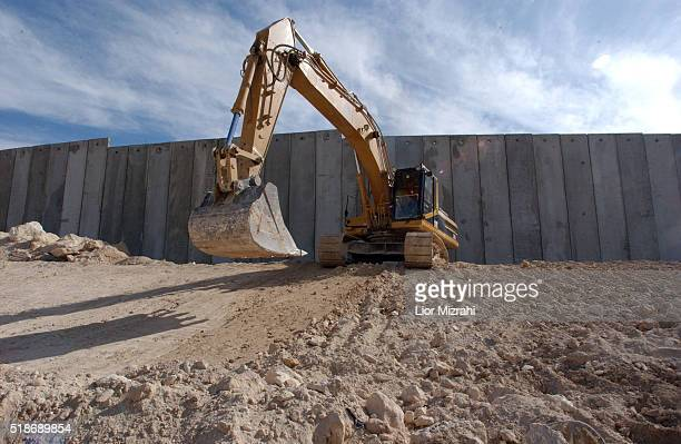 A bulldozer works next to the separation barrier between the West bank and Jerusalem in the East Jerusalem neighborhood of Atur Wednesday Dec 17 2003...