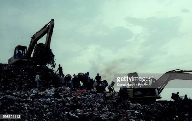 Bulldozers At Landfill With Garbage Against Sky