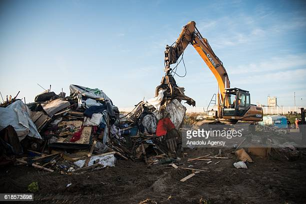 Bulldozers demolish the shops houses and buildings at the Calais 'jungle' camp during the fourth day of evacuation in Calais France on October 27...