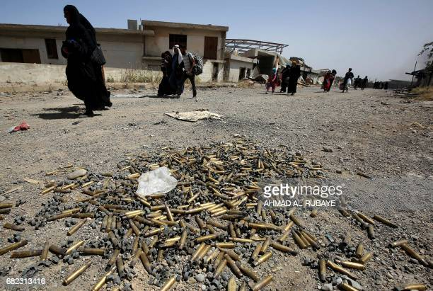 TOPSHOT Bullet cartridges lie on the ground as displaced Iraqis from western Mosul's alIslah alZaraye neighbourhood flee their area on May 12 2017...