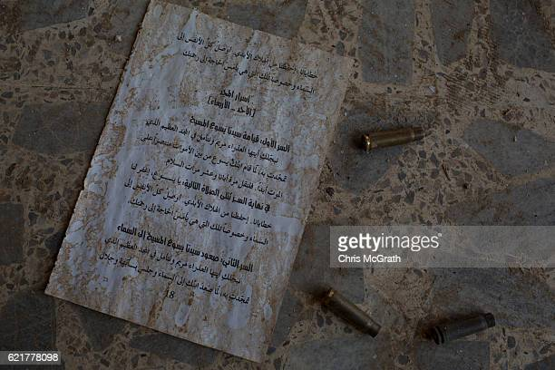Bullet casings are seen next to a sheet of Christian writings on the ground of the burnt and destroyed St Mary alTahira church on November 8 2016 in...