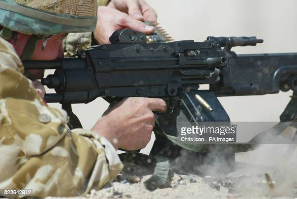 Bullet casings kick up sand as they fly out of the breach of a paratroopers Minimi machine gun on the live firing range in the Kuwaiti desert *...