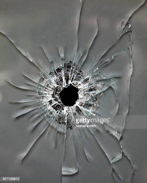 bullet hole in glass - agujero de bala fotografías e imágenes de stock