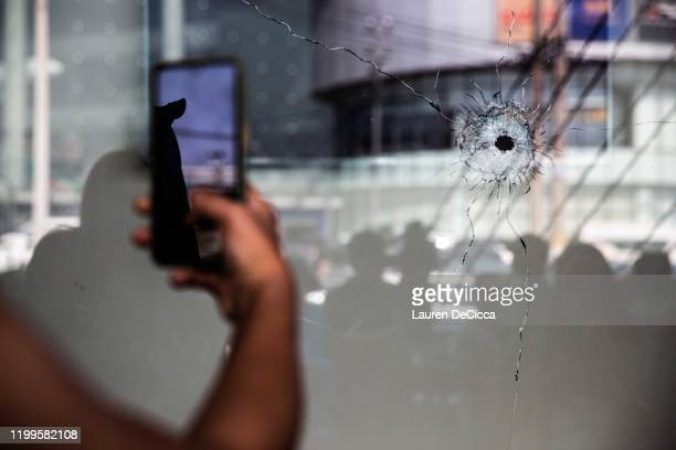 A bullet hole in the glass window of a shop across the street from Terminal 21 Mall following a mass shooting on February 9 2020 in Korat Thailand...