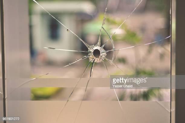 bullet hole on glass window - agujero de bala fotografías e imágenes de stock