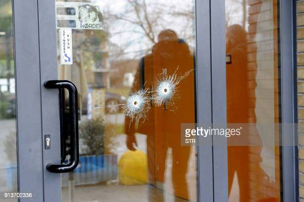 Bullet holes are seen in a glass door as police forensics officers carry out investigations in the area following the wounding of several foreign...