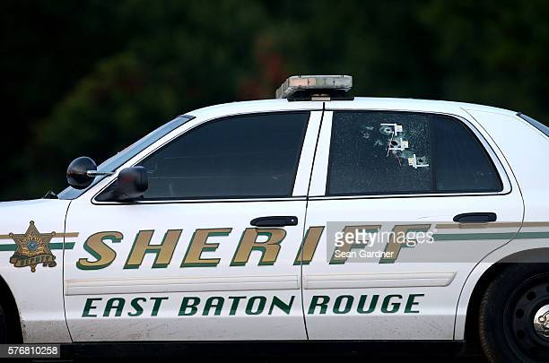 Bullet holes are seen in an East Baton Rouge police car as it's towed away from the scene where three police officers were killed this morning on...