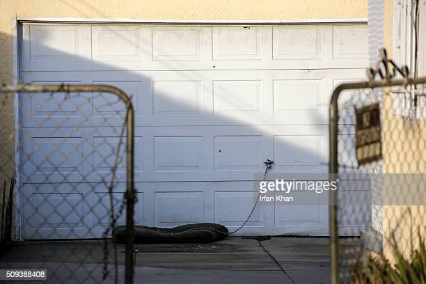 Bullet holes are seen in the garage door of the house where a yearold girl died in a shooting on 300 N Holly Avenue on February 10 2016 in Compton...