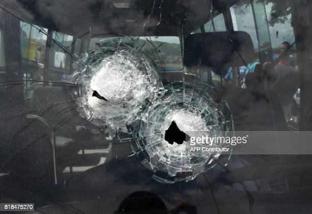 Bullet holes are seen on the windshield of a minibus after its driver was killed by gang members for refusing to pay them a war tax in Tegucigalpa on...