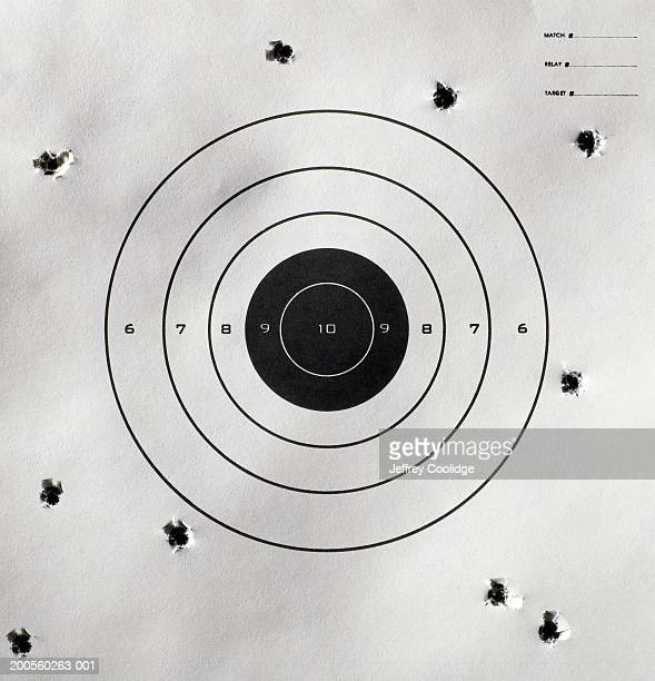 bullet holes around bull's-eye of shooting target - bullet hole stock pictures, royalty-free photos & images