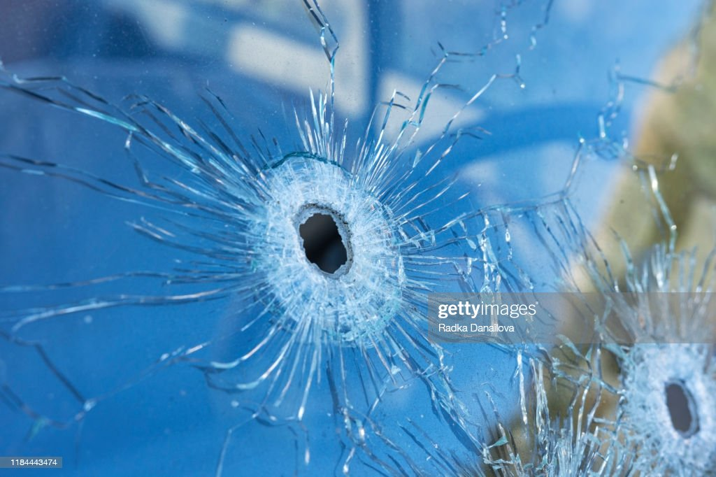 Bullet holes in the front safety glass of car. : Stock Photo