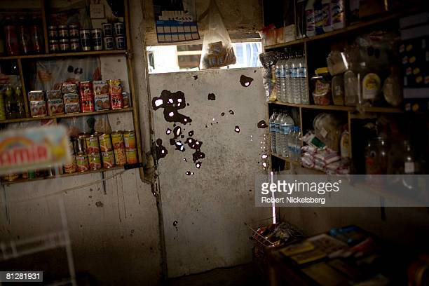 Bullet holes mark a door of a local shop in Sadr City across from a concrete wall recently erected by American forces look over destroyed and burned...