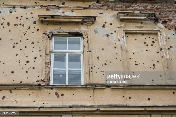 bullet holes on side of building - agujero de bala fotografías e imágenes de stock