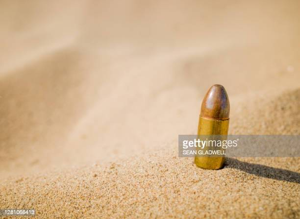 bullet in sand - shooting crime stock pictures, royalty-free photos & images