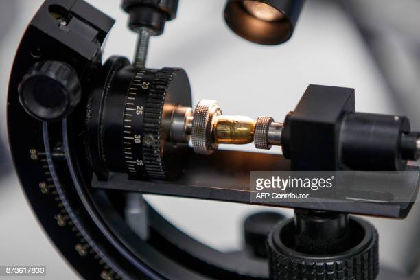 A bullet is seen whilst forensic officer matches firing details and references cartridge cases at the London Metropolitan Police firearm forensics...