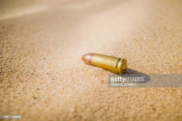 bullet on sand - gun control stock pictures, royalty-free photos & images