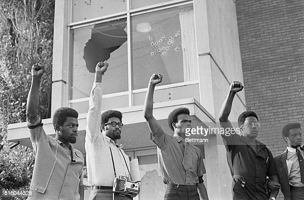 Bullet riddled Alexander Hall stands in background as youths give Black Power hand sign following memorial services for Phillip Gribbs and James...