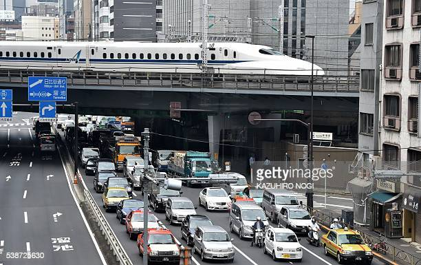 A bullet train runs on a railroad in Tokyo on June 8 2016 Japan's economy expanded at a slightly faster pace than first thought revised figures...