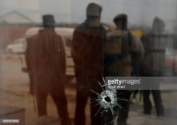 A bullethole is seen in a shop window near the site of a shooting by suspected militants in Srinagar on December 11 2013 One Indian paramilitary...