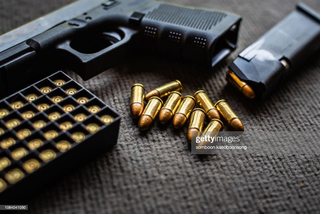 bullets and gun on black velvet desk : Stock Photo