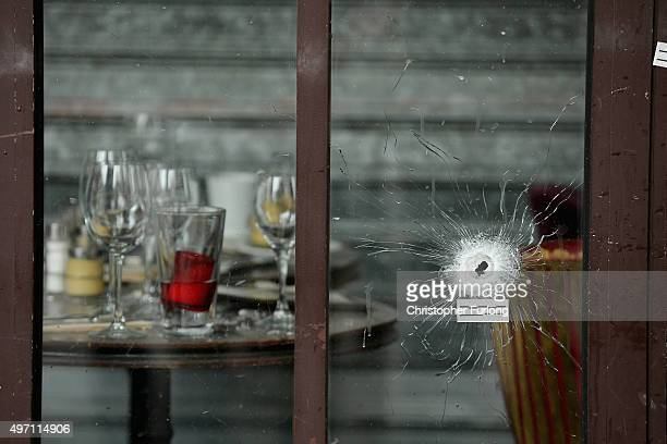 Bullets holes are seen through the glass door of a cafe near Casa Nostra after yesterday's terror attack on November 14, 2015 in Paris, France. At...