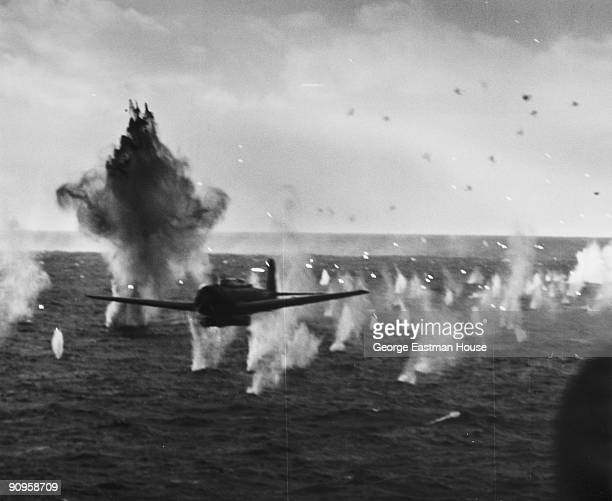 Bullets splash in the water behind it as a Japanese torpedo bomber flies low above the waves while escaping a trace of antiaircraft fire directed...