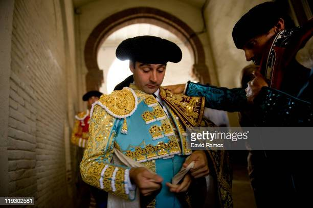 Bullfighter Enrique Ponce from Spain dresses up helped by his assistants before the third bullfight of the 2011 season at the Monumental bullring on...