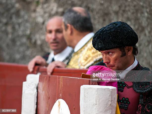 Bullfighter in a refuge in a bull ring looking fíjamente at the bull and with the cape bitten in the mouth by the nerves. Bocairent bullring (the...