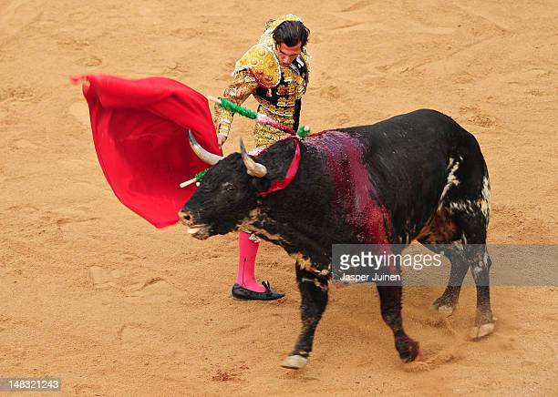 Bullfighter performs with a El Pilar fighting bull on the fourth day of the San Fermin runningofthebulls on July 10 2012 in Pamplona Spain
