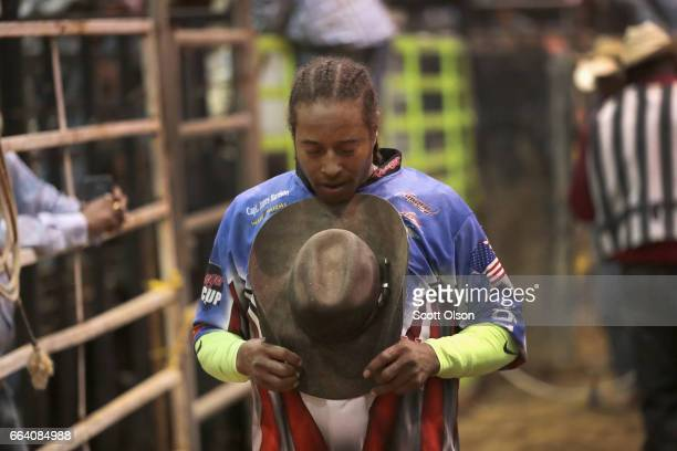 Bullfighter Teaspoon Mitchell says a prayer before the start of the bull riding competition at the Bill Pickett Invitational Rodeo on April 1 2017 in...