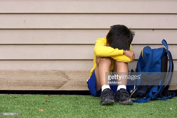 Bullied young boy sitting on grass with his head in his lap