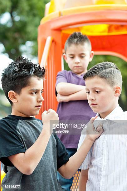 Les tyrans faire partie d'un garçon sur le toboggan