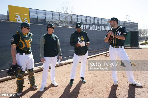 Bullpen Coach Marcus Jensen of the Oakland Athletics works with some of the pitchers and catchers during a spring training workout at Fitch Park on...