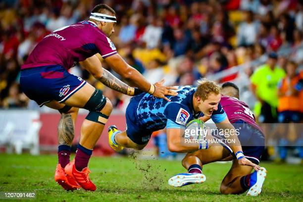 Bulls' Burger Odendaal is tackled by Reds' Scott Malolua during the Super Rugby match between Australia's Queensland Reds and South Africa's Bulls in...
