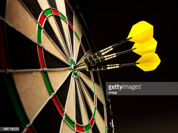bulls eye in a dartboard with yellow darts - dartboard stock pictures, royalty-free photos & images