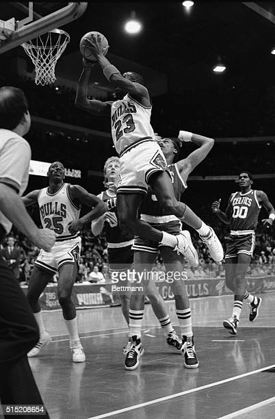 Bulls' Michael Jordan flies through the air in front of Celtics' Larry Bird and Dennis Johnson right behind Jordan in the first quarter of the game...