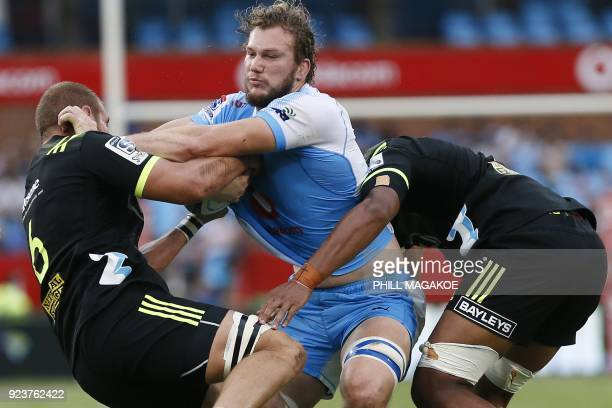 Bulls' RG Snyman is tackled by Hurricanes' captain Brad Shields and Sam Lousi during the SUPER XV Rugby match between Bulls and Hurricanes at Loftus...