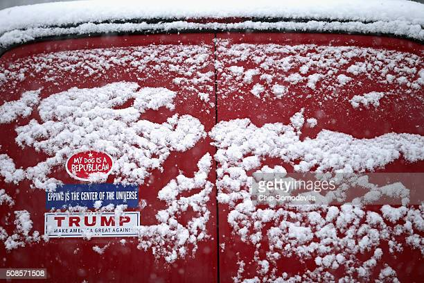 A bumper sticker for Republican presidential candidate Donald Trump on the back of a van is dusted with snow outside the Londonderry Lions Club where...