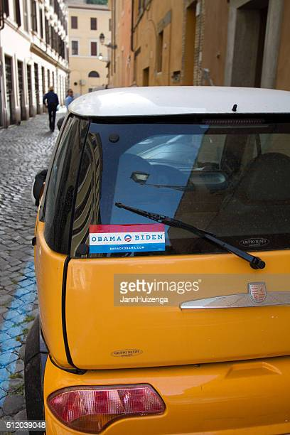 obama-biden bumper sticker on little yellow car, cobbled street, rome - bumper sticker stock photos and pictures
