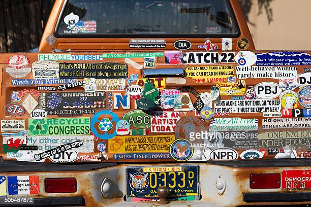 bumper stickers galore: back of veteran's rusty pickup truck - bumper sticker stock photos and pictures