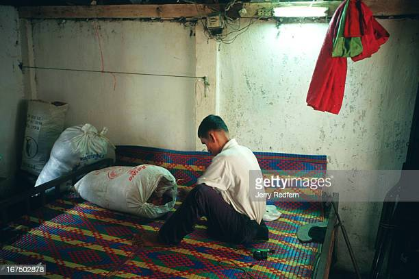Bun Na gathers the last of his possessions together in the small airless apartment he shared with his wife in Phnom Penh before leaving for Veal Thom...
