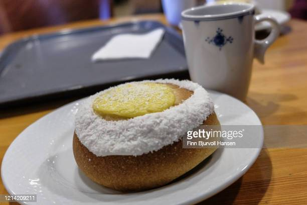 bun with custard, vanilla and coconut. cup of coffee in background - finn bjurvoll stock pictures, royalty-free photos & images