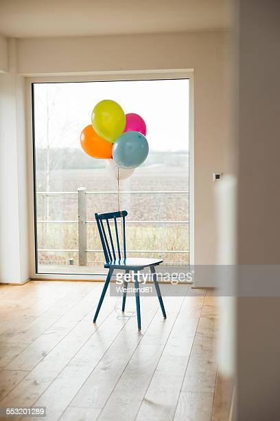 Bunch of balloons and chair by the window