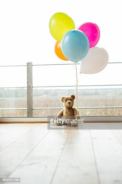 Bunch of balloons and teddy bear by the window