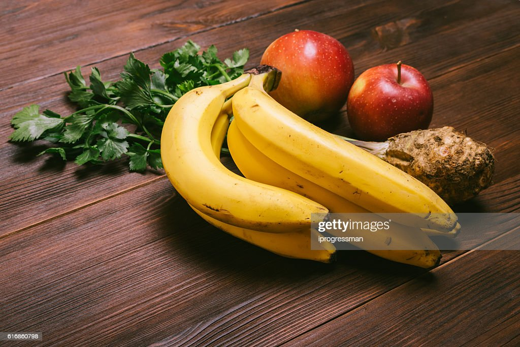 Bunch of bananas, celery root and red apples : Stock Photo