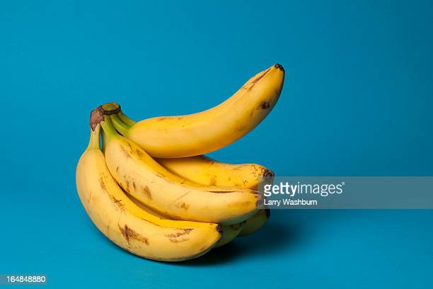 a bunch of bananas with one banana sticking up, suggestive of an erection - foreskin stock pictures, royalty-free photos & images