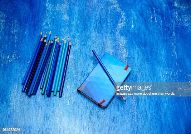 A bunch of blue pencils, a blue note pad over blue surface.