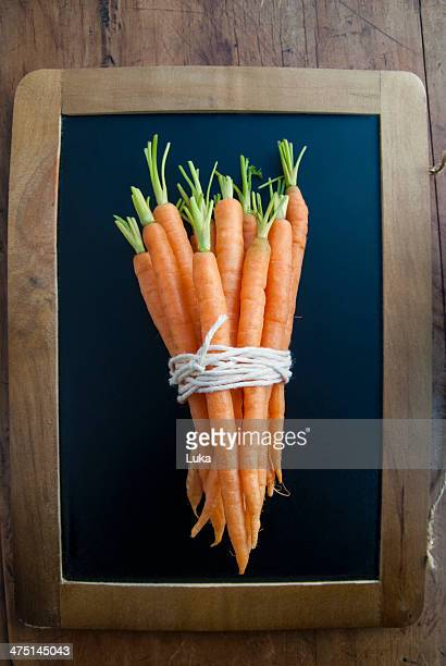 Bunch of carrots on blackboard, still life