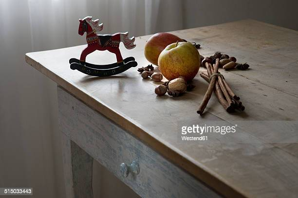 Bunch of cinnamon sticks, star anise, nuts, miniature rocking horse and two apples on wooden table
