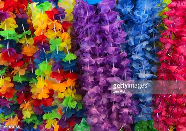 bunch of colorful fabric lei or floral garland on display for retail sale - hawaiian lei stock pictures, royalty-free photos & images